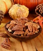 stock photo of pecan  - A wooden bowl of organic pecan halves on a holiday table - JPG