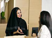 foto of arabian  - Arabian Receptionist helping a customer on the front desk - JPG