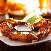 stock photo of chicken  - buffalo barbecue hot chicken wings around ranch sauce with celery - JPG