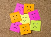 picture of smiley face  - smiley cartoon face expression on yellow post it note surrounded by sad and depressed faces on cork message board in happiness versus depression and smile against adversity concept - JPG