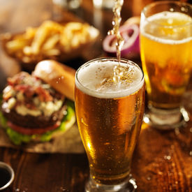 pic of burger  - pouting beer into glass with burgers on wooden table top - JPG