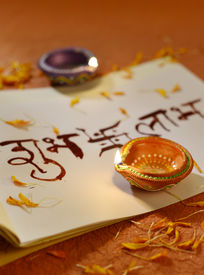 picture of sanskrit  - Indian traditional lamps placed on a book with Sanskrit calligraphy - JPG