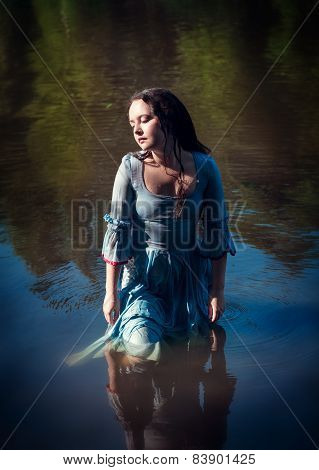 Young Beautiful Girl In Long Blue Dress Standing In The River
