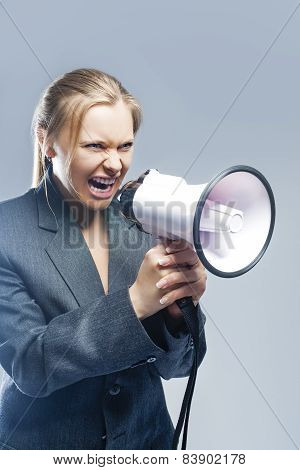 Furious Caucasian Blond Female In Suite Shouting Using Megaphone. Against Gray Background