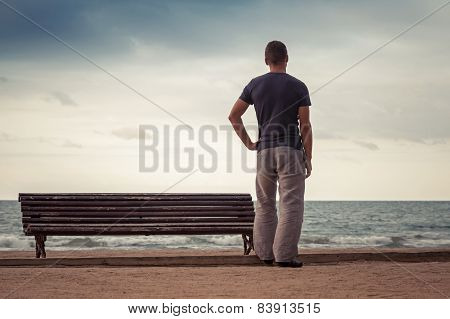 Young Man Stands Near Old Bench On The Sea Coast