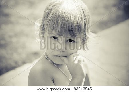 Portrait Of Cute Thinking Caucasian Blond Baby Gir
