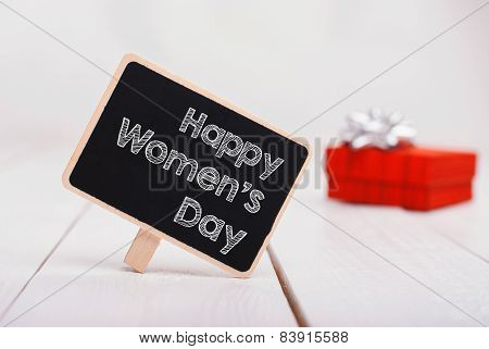 Isolated chalk board with inscription Happy womens Day and red gift on background. 8 march.Mothers D