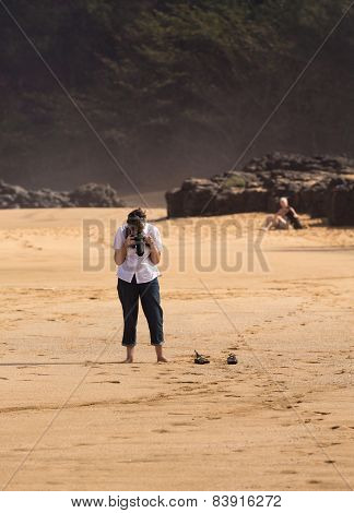 Senior Woman Takes Photo On Beach
