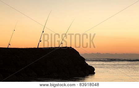 Three Fishing Rods At Sunset Over Ocean