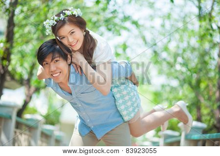 Young Man Giving A Piggy Back To His Girlfriend