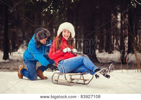 Positive Couple Sledding In Park