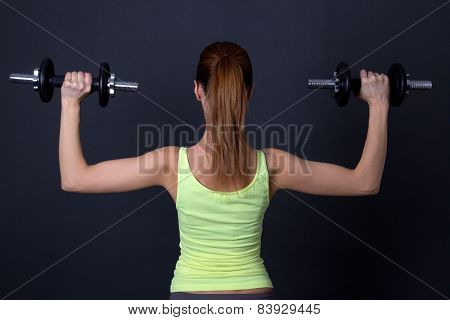 Back View Of Sporty Woman With Dumbbells Over Grey