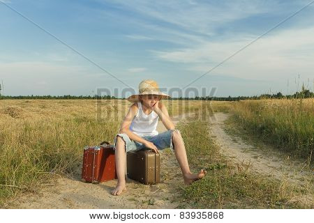 Teenage Traveler Waiting And Sitting On Luggage