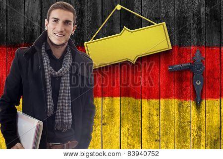 smiling student in front of wooden door with german flag