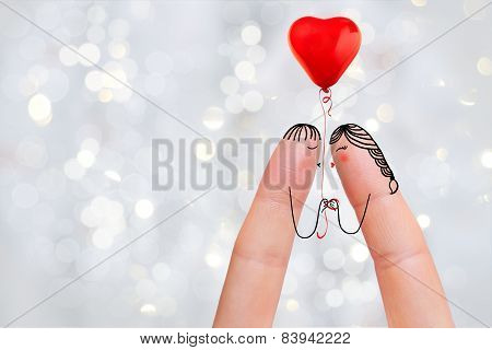 Conceptual finger art. Lovers are kissing and holding balloon. Stock Image