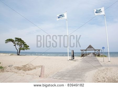 Ahus beach with flags and pier