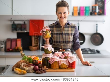 Portrait Of Happy Young Housewife With Jars Of Pickled Vegetable