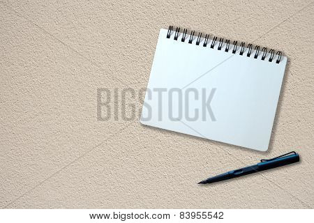 Notebook And Pen On Beige Plaster Texture