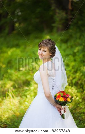 beautiful bride on the wedding day, holding a bouquet, in park