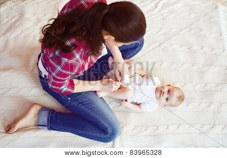 Little baby girl getting dressed by her mother