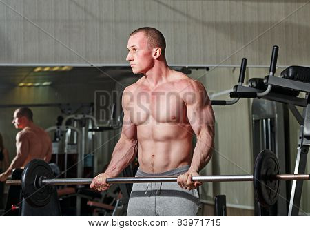 Man practicing with barbell in gym