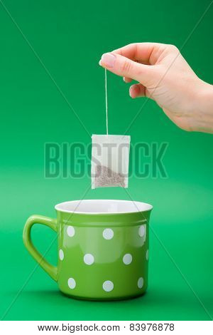 Hand Putting A Tea Bag Into