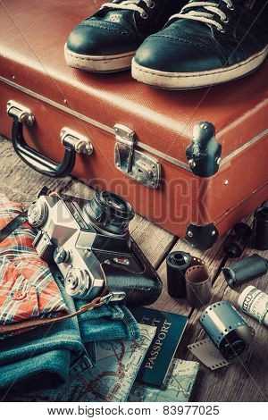 Old Travel Suitcase, Sneakers, Clothing, Map, Filmstrip And Retro Film Camera.