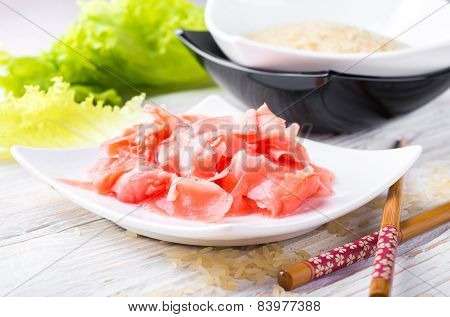 Red pickled ginger on a white plate, oriental cuisine