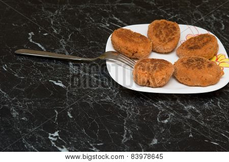 Cutlet And  A Fork On  White Plate On  Marble Table.