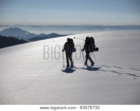 Men Go In Snowshoes In The Mountains.