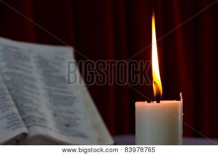 Bible Open On A Table With Candle