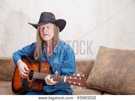Middle-aged Man In A Hat Plays Guitar And Sings