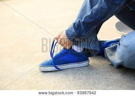 skateboarder tying shoelace at skate park