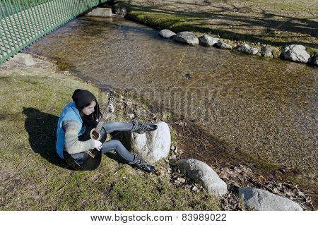 Playing Her Guitar By A Stream.
