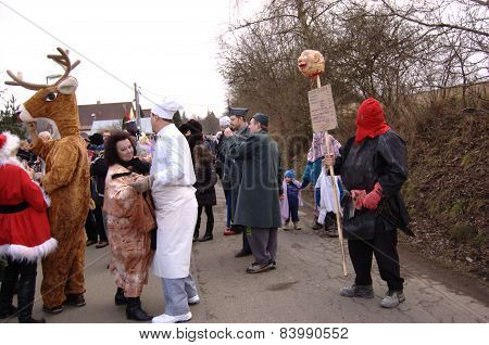 Participants of shrovetide parade, dancing on the village street.