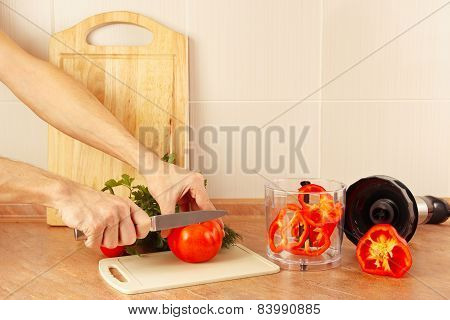 Hands chefs cut red tomato on kitchen table