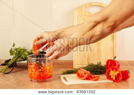 Hands chefs put chopped tomato in blender