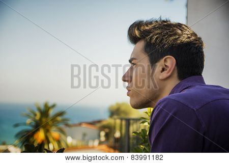 Attractive young man outdoor looking over a seaside landscape