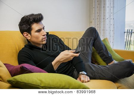 Young man sitting on couch watching television
