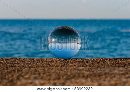 Glass transparent ball on sea background and grainy surface. Water