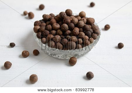 Whole Allspice Peppers On A White Table