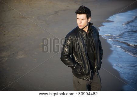 Attractive young man at the seaside on the beach wearing black leather jacket