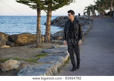 Handsome young man at the seaside along the shore by the ocean or sea