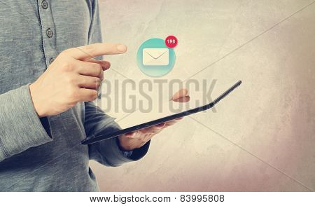 Young Man Pointing At An Email Icon Over A Tablet