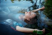 picture of corpses  - Young beautiful drowned woman in blue dress lying in the water outdoor - JPG