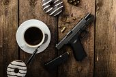 foto of cap gun  - American police officer morning donuts juice fresh black coffee and his gun - JPG