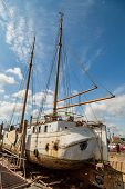 picture of dock  - Large old sailing boat undergoing serious repair work while docked on the quay - JPG