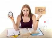 picture of time study  - young beautiful college student girl studying for university exam in stress asking for help holding alarm clock test deadline time pressure sitting on desk in education concept - JPG