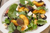 image of vinegar  - Plate of grilled peach and Mozzarella salad with mixed baby greens and balsamic vinegar in a rustic setting - JPG