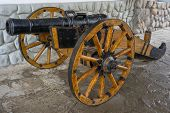 picture of artillery  - Old medieval artillery canon before a stone wall - JPG